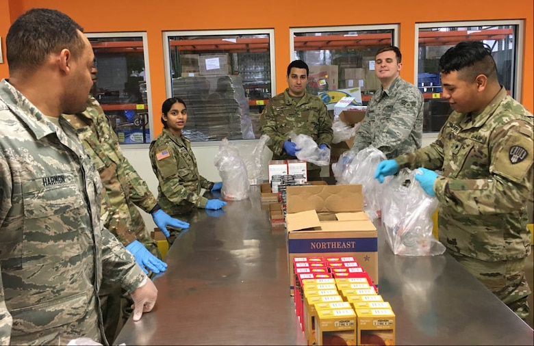 New York Air and Army National Guard members pack food parcels at a food pantry in Westchester County, N.Y., March 12, 2020, in support of state COVID-19 response efforts. Members were providing food to families to make up for school lunch and breakfast meals students are missing after schools in New Rochelle were closed to prevent the spread of the virus. (Photo by Col. Steve Rowe)
