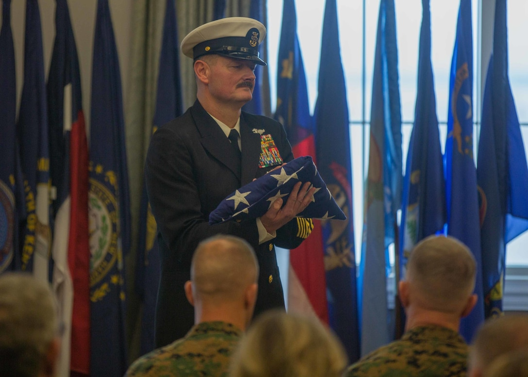 Navy Command Master Chief Christopher L. Hill carries a U.S. flag during a retirement ceremony at Marine Corps Air Station Cherry Point, North Carolina, March 6, 2020. Hill retired after 32 years of faithful service to the United States Navy. Hill is the outgoing Command Master Chief of 2nd Marine Aircraft Wing. (U.S. Marine Corps photo by Cpl. Ethan Pumphret)