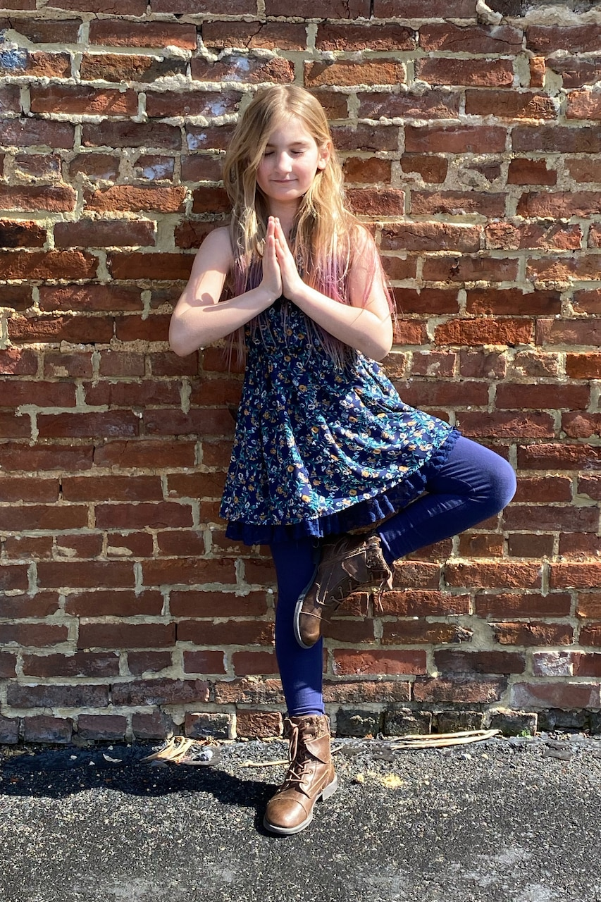A girl strikes a yoga pose in front of a brick wall.