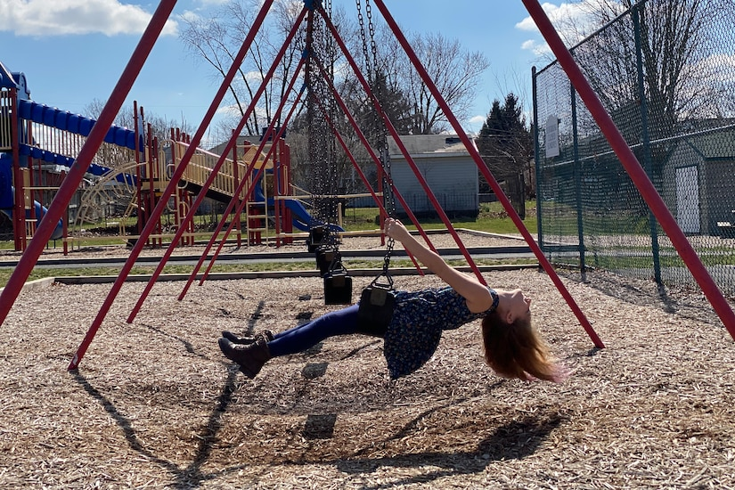 A girl is parallel to the ground while riding a swing at a playground.