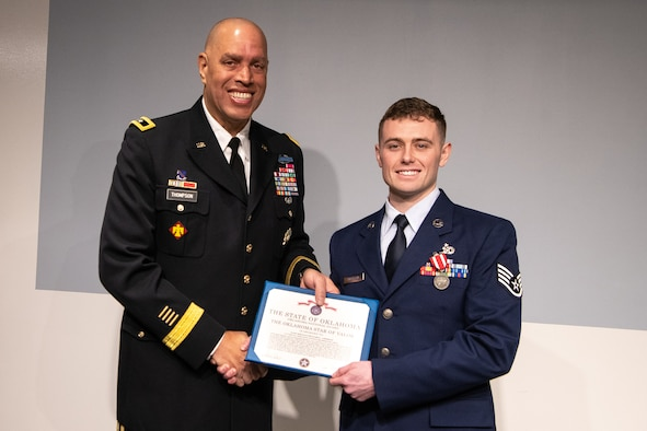 Maj. Gen. Michael Thompson (left), adjutant general for Oklahoma, and Staff Sgt. Benjamin Anderson (right), an air freight journeyman assigned to the 137th Special Operations Logistics Readiness Squadron, pose with the Oklahoma Star of Valor award during a ceremony March 7, 2020, at Will Rogers Air National Guard Base, Oklahoma City. Anderson was honored for his heroic actions when he saved a man from a burning vehicle April 29, 2018.