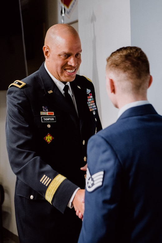 Major General Michael Thompson, Adjutant General for Oklahoma, presents a coin to Staff Sgt. Benjamin Anderson, an air freight journeyman assigned to the 137th Special Operations Wing Logistics Readiness Squadron, during an Oklahoma Star of Valor ceremony March 7, 2020, at Will Rogers Air National Guard Base, Oklahoma City. Anderson was honored for his heroic actions when he saved a man from a burning vehicle April 29, 2018.