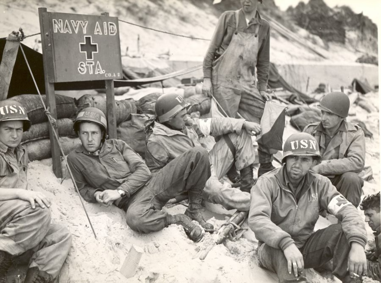 "A group of servicemen sit on the sand; a sign in the background reads, ""Navy Aid Sta."""