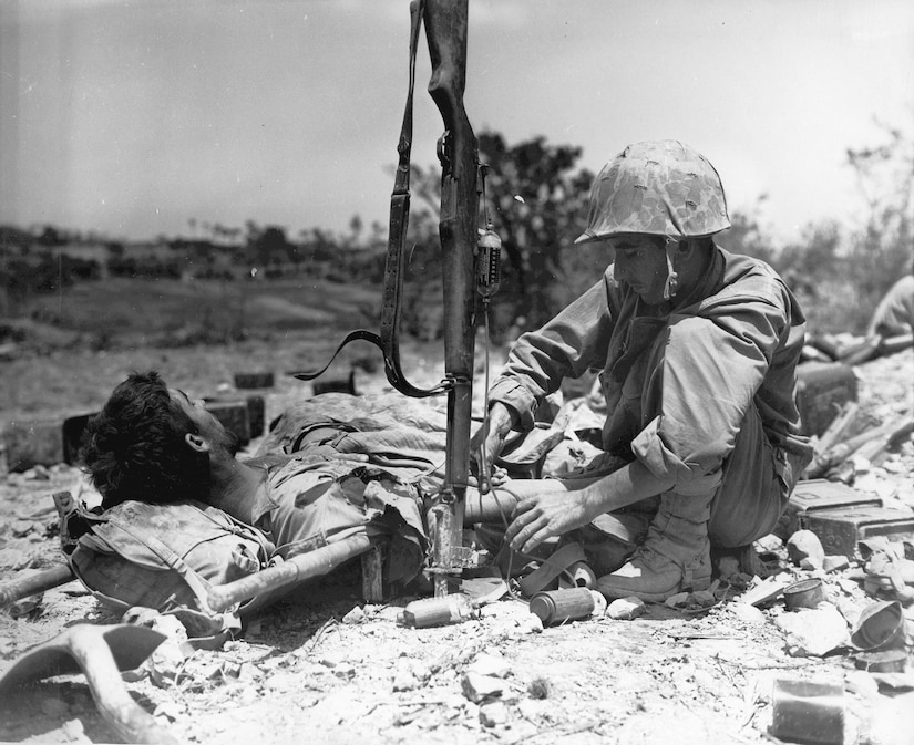 A wounded serviceman is attended by another service member.