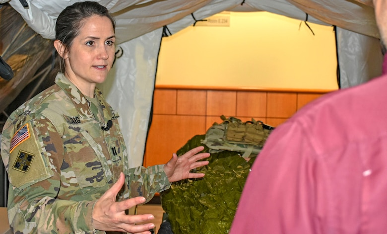 Woman in green camouflage uniform stands in a tent talking to person in red shirt.