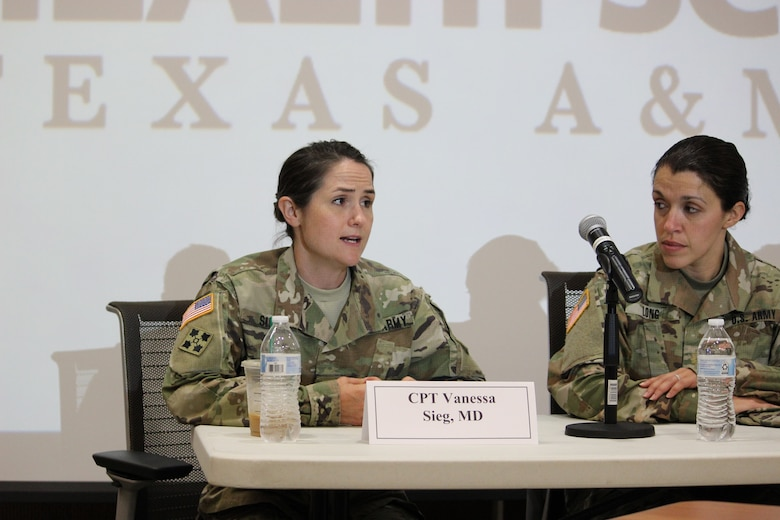 Two brown-haired women in green camouflage uniforms sit in black chairs behind a white table with a microphone.