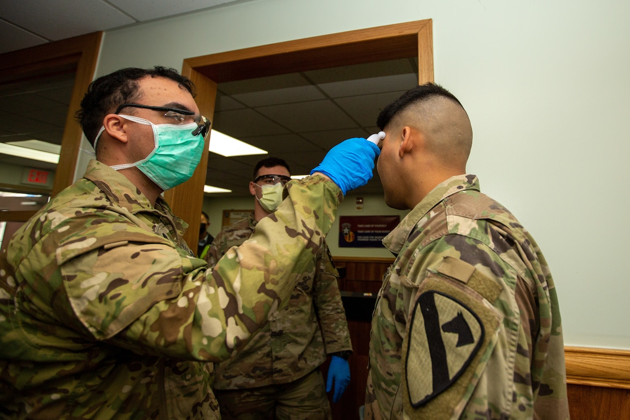 A uniformed soldier wears a face mask while taking the temperature of another soldier.