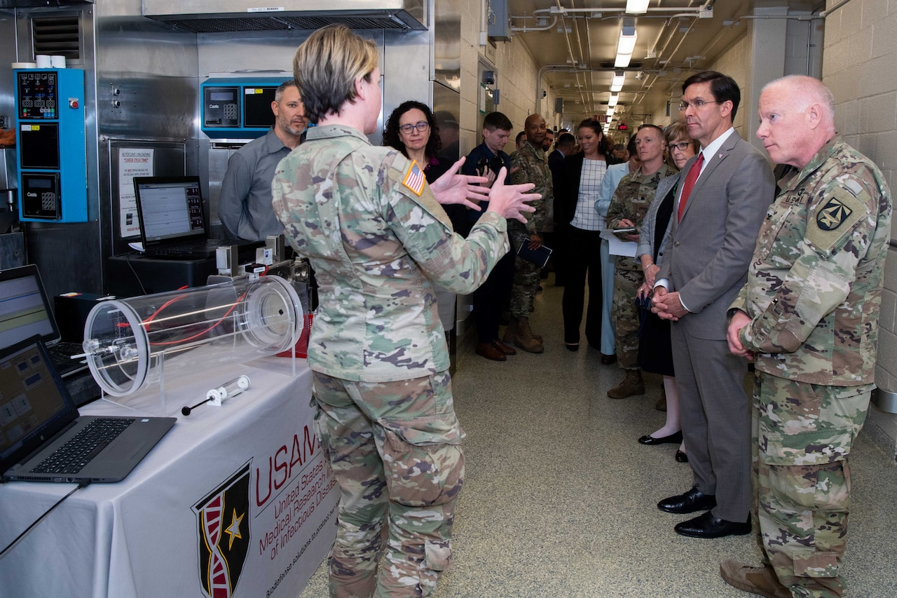 More than a dozen individuals stand facing a single female military member as she speaks about medical equipment on a table.
