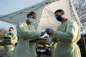 Photo of Airmen preparing for a drive-through health screening.