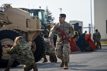 U.S. Air Force Senior Airman John Kuthmann, a patrolman with the 35th Security Forces Squadron, performs a status check with other Airmen after a simulated attack during an Agile Combat Employment practice capstone event at Misawa Air Base, Japan, March 13, 2020. During the event, Airmen switched out from assisting with other tasks to learn how to perform security patrols and defend their position. (U.S. Air Force photo by Tech. Sgt. Timothy Moore)
