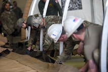 U.S. Airmen from various unit of the 35th Fighter Wing work together to build a small shelter system tent during an Agile Combat Employment practice capstone event at Misawa Air Base, Japan, March 13, 2020. The ACE concept requires units to deploy small teams to austere locations. As such, Airmen are training to be able to assist in completing tasks outside of their normal career functions. (U.S. Air Force photo by Tech. Sgt. Timothy Moore)
