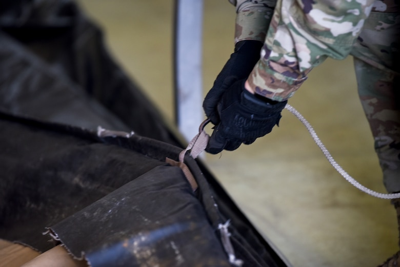 A U.S. Airman connects a rope to the tarp of a small shelter system tent during an Agile Combat Employment practice capstone event at Misawa Air Base, Japan, March 13, 2020. The ACE concept requires units to deploy small teams, who will be able to build their own shelters, pack their own cargo for shipping, and generally conduct operations from any austere location. (U.S. Air Force photo by Tech. Sgt. Timothy Moore)