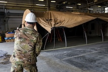 A U.S. Airman pulls the tarp of a small shelter system tent over its frame during an Agile Combat Employment practice capstone event at Misawa Air Base, Japan, March 13, 2020. The ACE concept requires units to deploy small teams, who will be able to build their own shelters, pack their own cargo for shipping, and generally conduct operations from any austere location. (U.S. Air Force photo by Tech. Sgt. Timothy Moore)