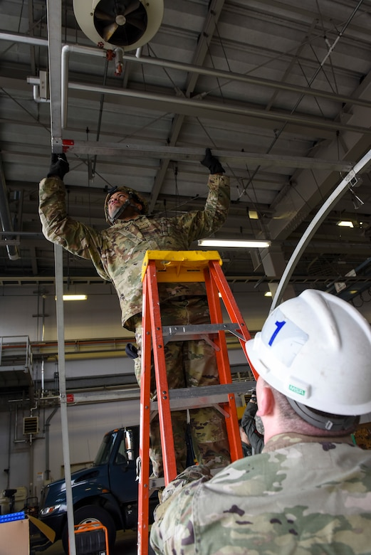 U.S. Air Force Airman Cameron Coughlin, a structures technician with the 35th Civil Engineer Squadron, holds a ladder for Senior Airman Kenneth Brown, an alarm monitor with the 35th Security Forces Squadron, as he connects the beams on a small shelter system tent during an Agile Combat Employment practice capstone event at Misawa Air Base, Japan, March 13, 2020. The ACE concept requires units to be able to deploy small teams to austere locations. As such, Airmen are training so they can assist in completing tasks outside of their normal career functions. (U.S. Air Force photo by Tech. Sgt. Timothy Moore)