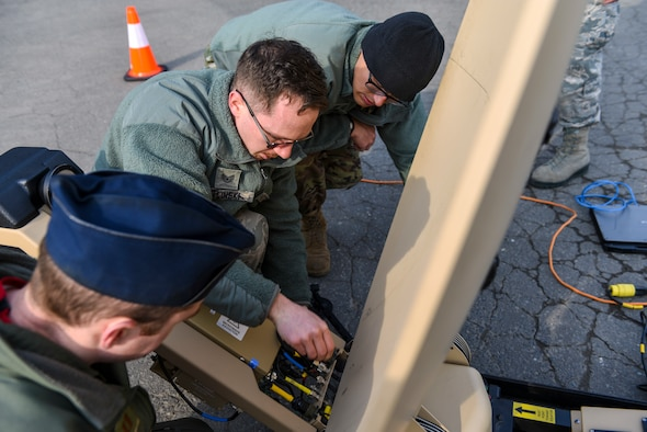U.S. Air Force Staff Sgt. Barry Zielinski, a cyber transportation supervisor with the 35th Communications Squadron, shows Capt. Joseph Holloway, a pilot with the 13th Fighter Squadron, and 1st Lt. Jordan Garcia, an assistant unit deployment manager with the 14th Fighter Squadron, how to set up a Hawkeye III antenna at Misawa Air Base, Japan, March 13, 2020. Zielinski showed the two officers how to set up the antenna as part of a practice capstone event for the Agile Combat Employment training for Misawa Airmen. (U.S. Air Force photo by Tech. Sgt. Timothy Moore)