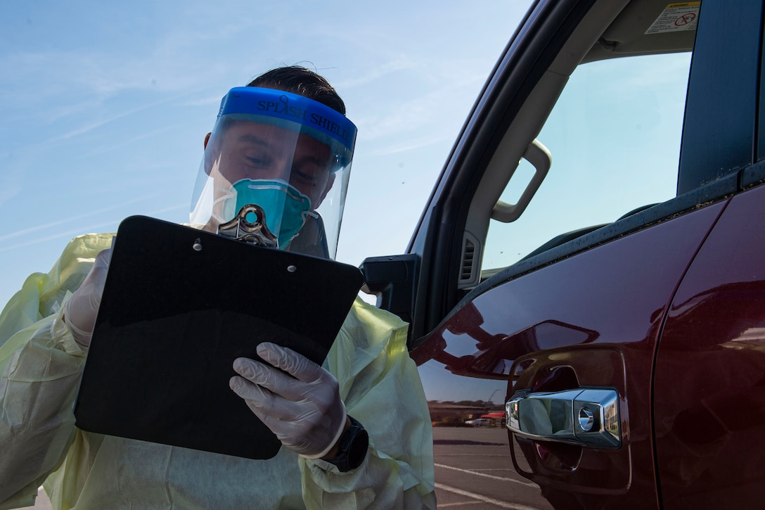 Photo of an Airman asking an active duty Airman questions during a drive-through health screening.