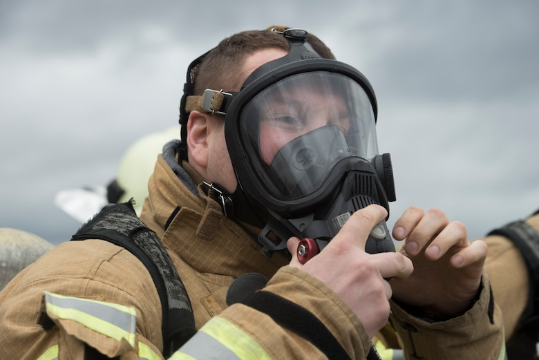 Photo of firefighter putting on gas mask.