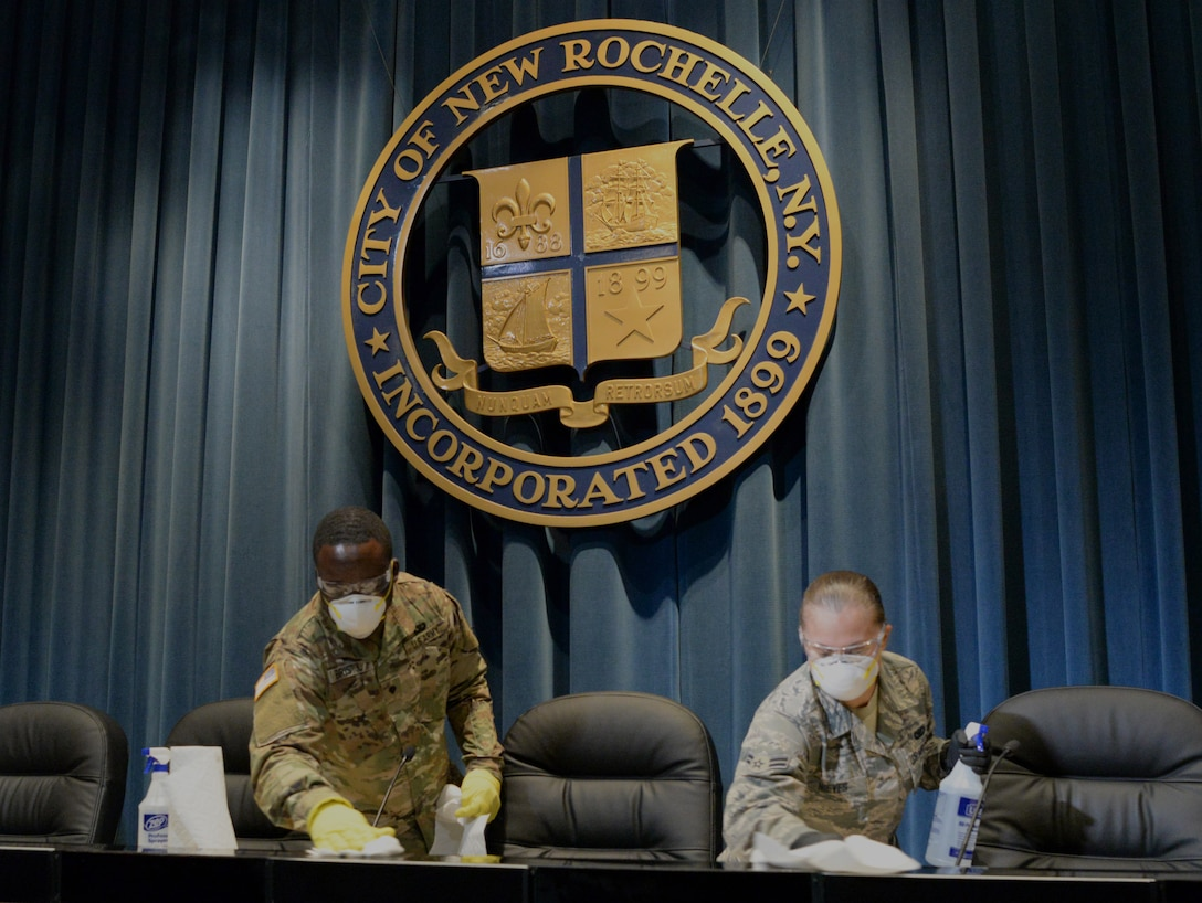 U.S Army Spc.Sherman Bristol, left, a member of the New York Army National Guard's 4th Finance Detachment, and Airman 1st Class Nieves, right, assigned to the New York Air National Guard's 106th Rescue Wing, help clean City Hall  in New Rochelle, New York, March 14, 2020. More than 900 New York National Guard members are supporting the multi-agency response to COVID-19. (U.S. Air National Guard photo by Senior Airman Sean Madden)