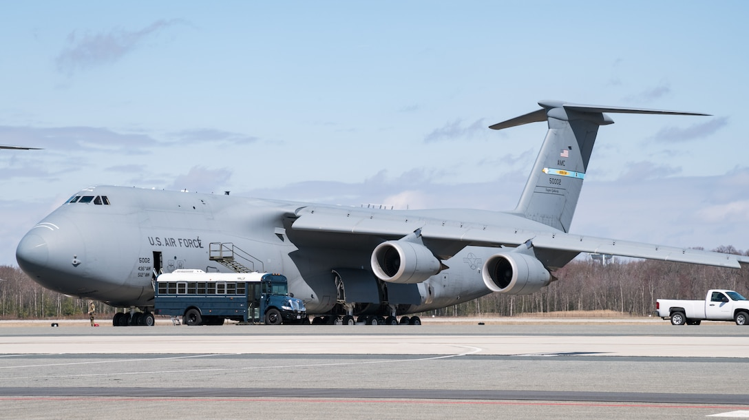 A bus parks in front of a C-5M Super Galaxy March 17, 2020, on Dover Air Force Base, Delaware. Normal daily operations continued as Team Dover members took preventative measures against the spread of COVID-19. (U.S. Air Force photo by Roland Balik)