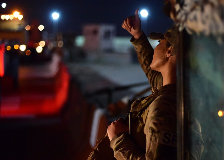 Airman signals to a vehicle convoy