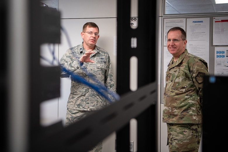 Col. Scott Townsend (left), 205th Engineering and Installation Squadron (205th EIS) commander, speaks to U.S. Air Force Lt. Gen. Jim Slife (right), commander of Air Force Special Operations Command, Hurlburt Field, Fla., about an innovation of 205th Airmen during an immersion tour of the 137th Special Operations Wing at Will Rogers Air National Guard Base in Oklahoma City, March 7, 2020. Several 205th EIS Airmen developed and designed the Cyber Training Retention Operations Network, which is a comprehensive and cost-effective program that provides hands-on training in place of simulations. (U.S. Air National Guard photo by Tech. Sgt. Kasey M. Phipps)