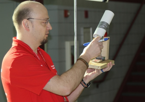 Christopher Strunk, chief of military design, Tulsa District, U.S. Army Corps of Engineers reviews a ping pong ball launcher submission entry during the 2020 Tulsa Engineering Challenge at Tulsa Technical Institue, March 6.