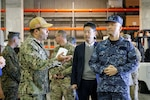 "Navy Cmdr. Allen ""AJ"" Rivera, commander of Defense Logistics Agency Distribution Yokosuka, Japan, explains how the agency provides superior storage and distribution solutions during a Feb. 28 visit with Navy Rear Adm. Satoshi Abe, Director General J4 Japan Joint Staff."