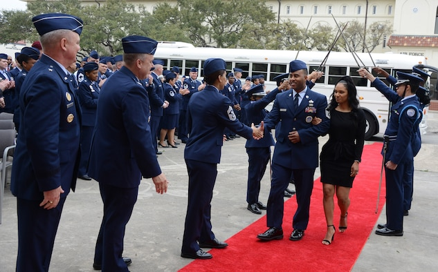 Master Sgt. Marquise Heard, 367th Recruiting Group, Robins Air Force Base, Georgia, and his wife Sofia walk through the guantlet as he is recognized as a Blue Suitor in front of headquarters Air Force Recruiting Service, Joint Base San Antonio- Randolph, Texas. (Air Force photo/Master Sgt. Chance Babin)