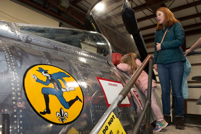 """A woman and child view an F-84  Thunderjet static display at the annual """"Women Take Flight"""" event held at the New England Air Museum , Windsor Locks, Connecticut, March 7, 2020. The aircraft was assigned to the 103rd Fighter Group during the Cold War. (U.S. Air National Guard photo by Tech. Sgt. Tamara R. Dabney)"""