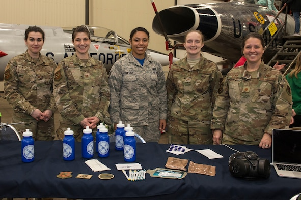 """Female airmen assigned to the 103rd Airlift Wing operate a display booth at the annual """"Women Take Flight"""" event held at the New England Air Museum , Windsor Locks, Connecticut, March 7, 2020.  """"Women Take Flight"""" is targeted toward girls who are interested in avionics and other STEM related fields.(U.S. Air National Guard photo by Tech. Sgt. Tamara R. Dabney)"""