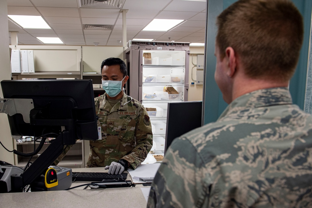 Photo of an Airman locating a patient's prescription.