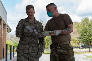 Photo of Airmen discussing a patient's prescription during a pick-up line.
