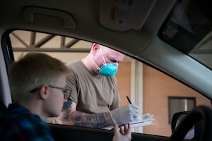 Photo of an Airman assisting a patient during a prescription pick-up line.
