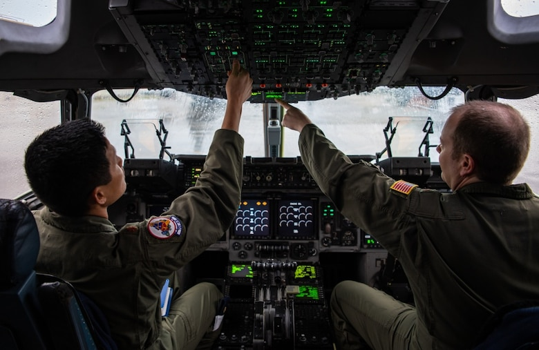 U.S. Air Force Maj. Tien Phung (left) and Maj. Stan Schmotzer (right), 701st Airlift Squadron C-17A Globemaster III pilots, perform pre-flight checks on the aircraft before conducting a local training sortie at Joint Base Charleston, S.C. March 5, 2020.