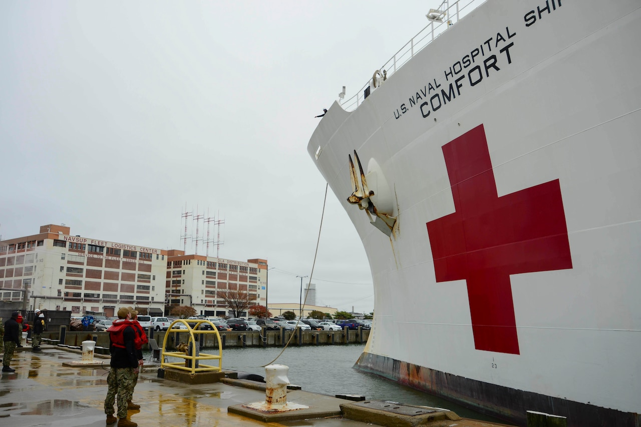 "A large white ship is tied to a dock. The ship has the words ""U.S. Naval Hospital Ship Comfort"" on the side, along with a large red cross."