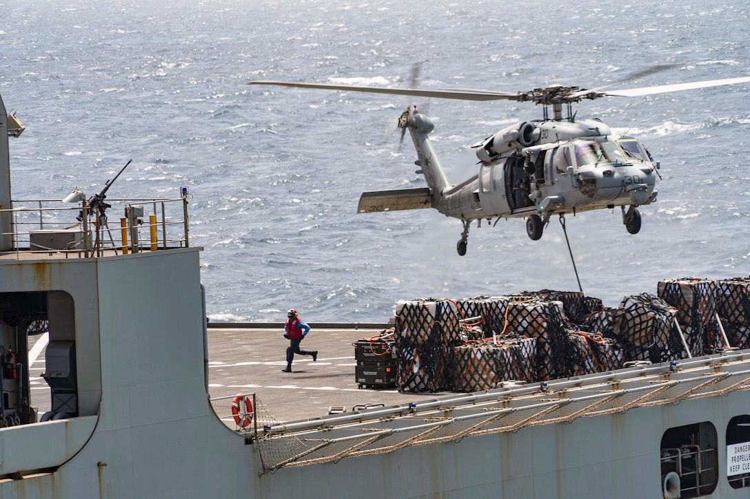 A helicopter hovers over cargo from a ship at sea.