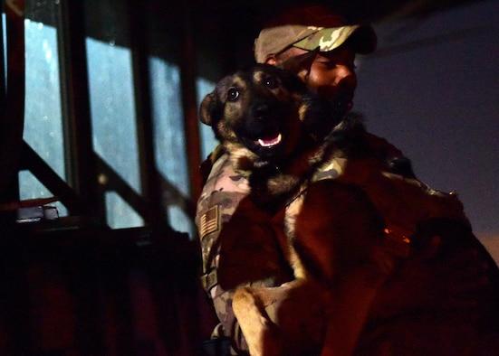 Dog handler embraces his canine