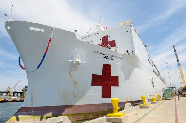 "A large white ship is tied to a dock. The ship has the words ""U.S. Naval Hospital Ship Mercy"" on the side, along with a large red cross."