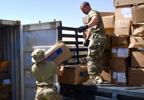 U.S. Air Force Airmen assigned to the 378th Expeditionary Contracting Squadron load a flatbed truck with contract purchases at the mailroom on Prince Sultan Air Base, Kingdom of Saudi Arabia, Mach 10, 2020. Members of the 378 ECONS are responsible for soliciting and acquiring the services and materials needed for most construction projects and services on PSAB. (U.S. Air Force by Tech. Sgt. Michael Charles)