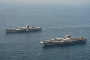 The aircraft carriers USS Dwight D. Eisenhower (CVN 69), left, and USS Harry S. Truman (CVN 75) transit the Arabian Sea March 18, 2020. The Harry S. Truman Carrier Strike Group is deployed to the U.S. 5th Fleet area of operations in support of naval operations to ensure maritime stability and security in the Central Region, connecting the Mediterranean and the Pacific through the Western Indian Ocean and three strategic choke points.
