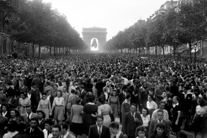 Crowds of people gather on a main street in Paris.