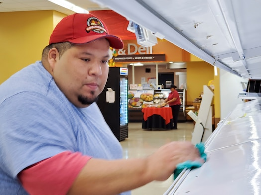 Albert Espinoza, Laughlin Air Force Base, Texas commissary meat department head, disinfects a store shelf at the store Mar. 19, 2020. In response to the outbreak in other parts of the country, Laughlin Air Force Base, Texas, has made modifications to its daily operations starting March 16 to keep the base operational while protecting the health and wellness of its Airmen, their families, the local community, and everyone who visit the base.