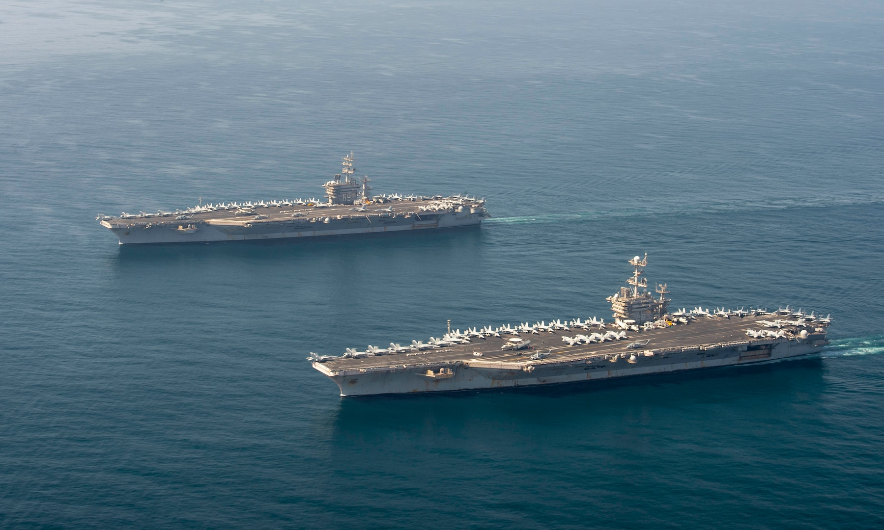 The aircraft carriers USS Dwight D. Eisenhower (CVN 69), top, and USS Harry S. Truman (CVN 75) transit the Arabian Sea March 18, 2020. The Harry S. Truman Carrier Strike Group is deployed to the U.S. 5th Fleet area of operations in support of naval operations to ensure maritime stability and security in the Central Region, connecting the Mediterranean and the Pacific through the western Indian Ocean and three strategic choke points.