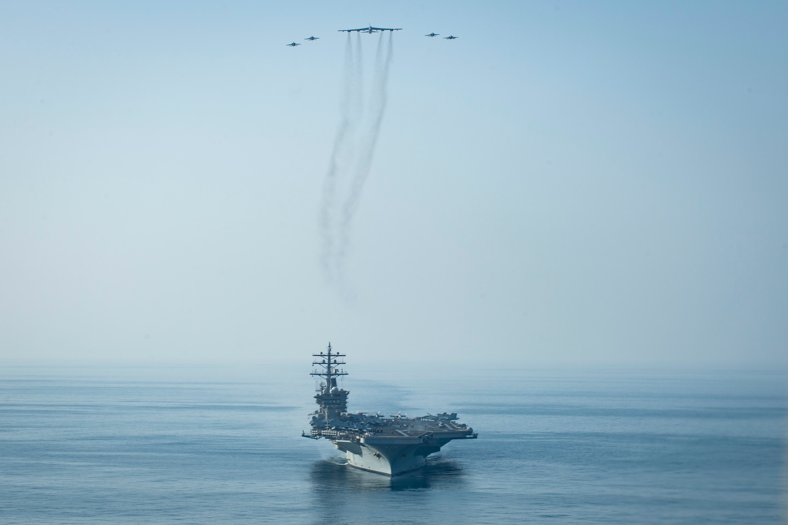 The aircraft carrier USS Dwight D. Eisenhower (CVN 69) conducts a combined air wing operation with a B-52 Bomber from U.S. Air Forces Central Command in the Arabian Sea, March 18, 2020. Ike is deployed to the U.S. 5th Fleet area of operations in support of naval operations to ensure maritime stability and security in the Central Region, connecting the Mediterranean and Pacific through the Western Indian Ocean and three strategic choke points.