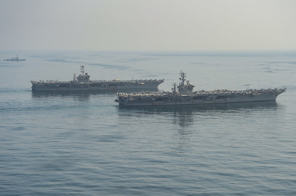 The aircraft carriers USS Dwight D. Eisenhower (CVN 69), front, and USS Harry S. Truman (CVN 75), center, and the guided-missile destroyer USS Lassen (DDG 82) transit the Arabian Sea March 18, 2020. The Harry S. Truman Carrier Strike Group is deployed to the U.S. 5th Fleet area of operations in support of naval operations to ensure maritime stability and security in the Central Region, connecting the Mediterranean and the Pacific through the Western Indian Ocean and three strategic choke points.