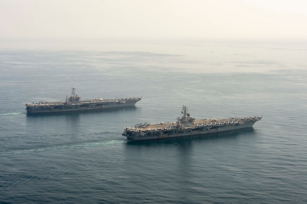 The aircraft carriers USS Dwight D. Eisenhower (CVN 69), front, and USS Harry S. Truman (CVN 75) transit the Arabian Sea March 18, 2020. The Harry S. Truman Carrier Strike Group is deployed to the U.S. 5th Fleet area of operations in support of naval operations to ensure maritime stability and security in the Central Region, connecting the Mediterranean and the Pacific through the Western Indian Ocean and three strategic choke points.