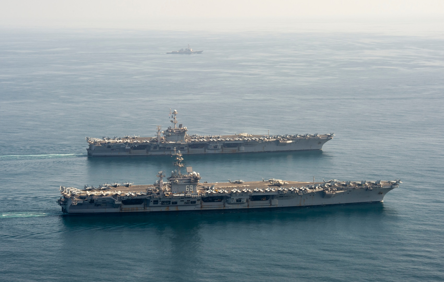 The aircraft carriers USS Dwight D. Eisenhower (CVN 69), front, and USS Harry S. Truman (CVN 75), and the guided-missile destroyer USS Lassen (DDG 82) transit the Arabian Sea March 18, 2020. The Harry S. Truman Carrier Strike Group is deployed to the U.S. 5th Fleet area of operations in support of naval operations to ensure maritime stability and security in the Central Region, connecting the Mediterranean and the Pacific through the western Indian Ocean and three strategic choke points.