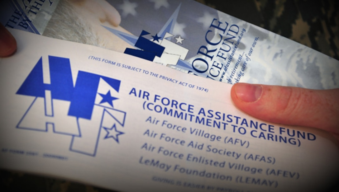 Close up of two people holding brochures for the Air Force Assistance Fund