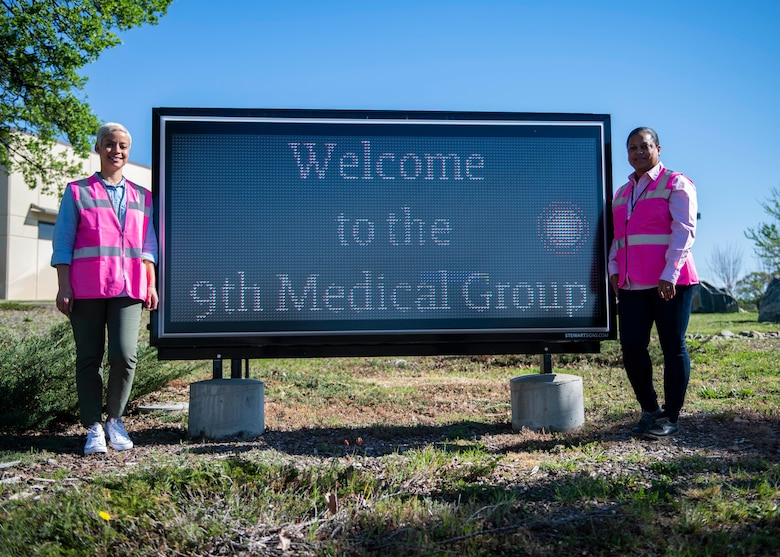 Lynn Bergmann, 9th Medical Group patient safety program coordinator, and Denise Ross, 9th MDG Patient Advocate, pose for a photo in front of the clinic's marquee on Beale Air Force Base, California.