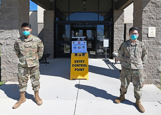 Airman Leon Guico, Left, 9th Medical Group (MDG) health administrator, and Senior Airman Christopher Miracle, 9th MDG optometry technician, guard the Entry Control Point (ECP) at the Clinic on Beale Air Force Base, California, Mar. 12, 2020. The ECP was set up at the Beale Clinic to protect Airmen and their families from the growing COVID-19 threat. (U.S. Air Force photo by Airman 1st Class Luis A. Ruiz-Vazquez)